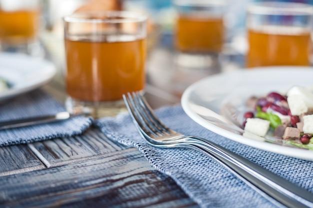 Подается на обед в ресторане, салат из вареных яиц, фасоль и крекеры, сок в стаканах и хлеб в плетеной корзине. концепция здорового питания, красивый интерьер, вкусная еда