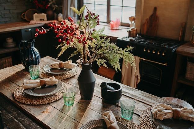 プレートナプキンの花瓶が付いた素敵な装飾のダイニングテーブルを提供しています。キッチンの背景のインテリア。ケータリングのコンセプト。レトロなスタイル。インテリア・デザイン