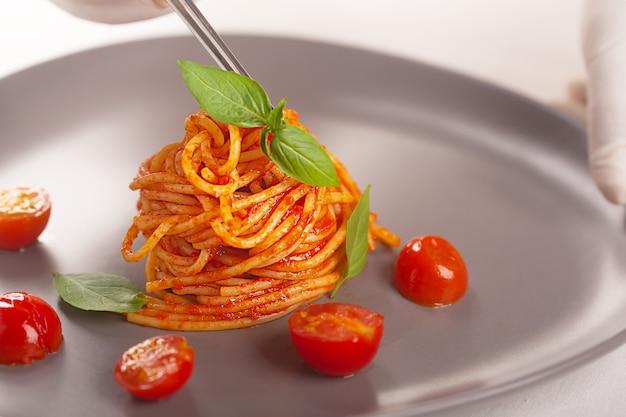 Подается паста в томатном соусе с помидорами черри и зеленью.