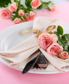 Подается тарелка с салфеткой и крупным планом розы. сервировка свадебного стола