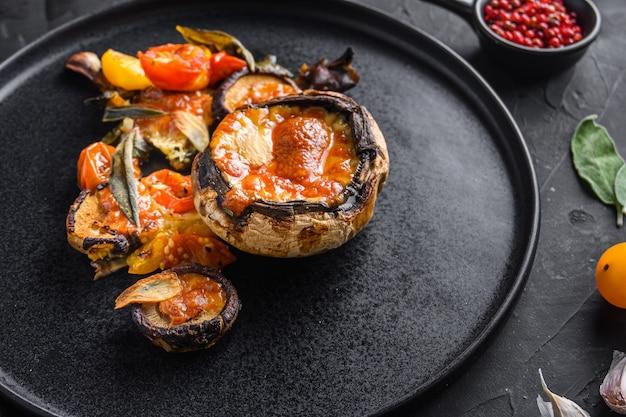 구운 포토 벨로 버섯을 제공하고 체다 치즈, 체리 토마토, 세이 지와 검은 배경 측면보기 위에 검정 잉크 판에 박제.