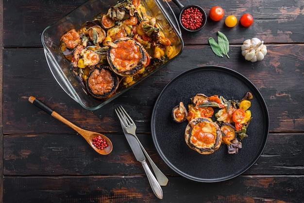 提供されるポートベローマッシュルーム、焼き、チェダーチーズ、チェリートマト、セージを詰めた古い木製の暗い背景の上面に黒い皿にセージ