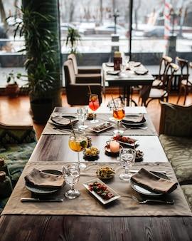 Сервированный столик в ресторане с аперитивными коктейлями и средиземноморскими закусками