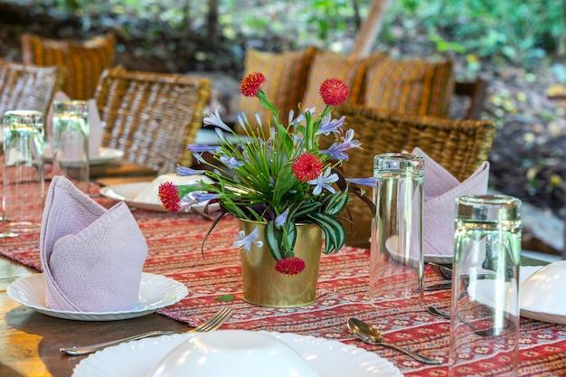 Сервированный стол и стулья из ротанга на пустой террасе ресторана. танзания, восточная африка