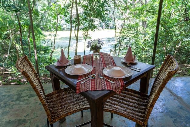 Обслуживают стол и два ротанговых стула на пустой террасе ресторана. танзания, восточная африка