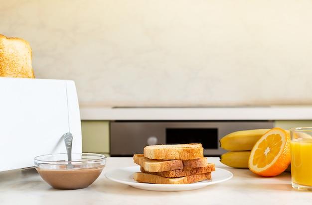 Served table for breakfast with toast, fruit, orange juice, peanut paste.