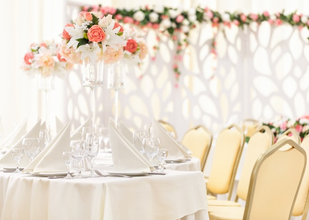 Served table for event dinner with cutlery and glasses, decorated with floral compositions in vases.
