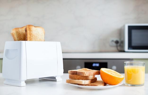Сервированный стол на завтрак с тостами, фруктами, апельсиновым соком.