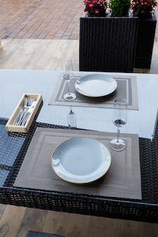 레스토랑에서 2인용 테이블을 제공합니다. 음식용 파란색 접시, 두 잔. 낭만적인 저녁 개념