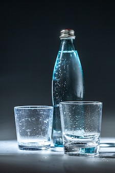 Served table set of mineral water bottle and glasses