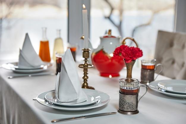 복고풍 컵에 차 한 잔과 함께 테이블을 제공합니다. 클로즈업, 선택적 초점