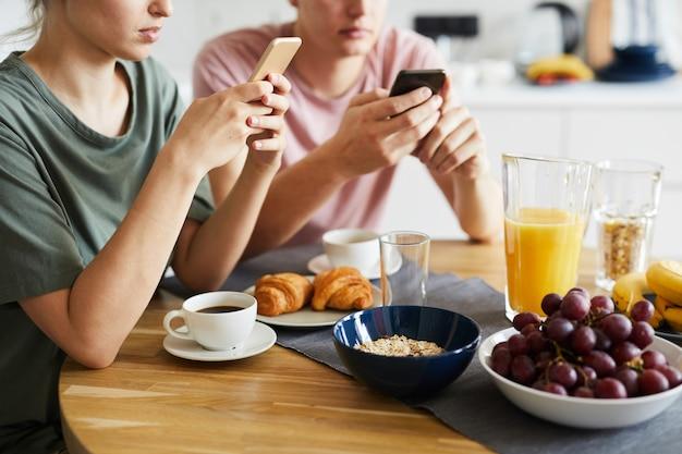 食品とスマートフォンを使用して若いカップルを添えてテーブル