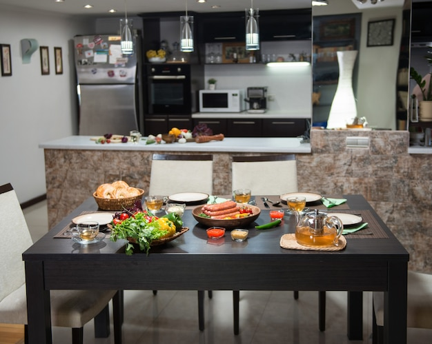 Served table with food and sausages in the home kitchen