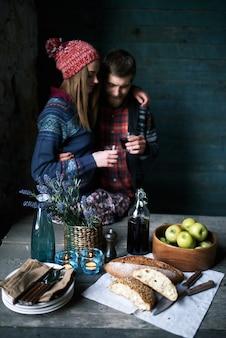 自家製のパンとワイン、ボウルにリンゴ、皿、野花を添えたテーブルと、屋内でバックグラウンドで乾杯する若いカップル
