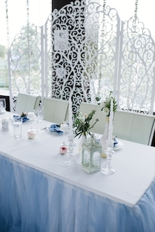 Served for wedding banquet table in blue white. wedding decoration. blue napkin with flower on a white plate. openwork arch.