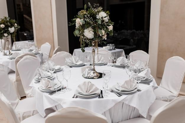レストランで花のセンターピースと白い丸テーブルを提供