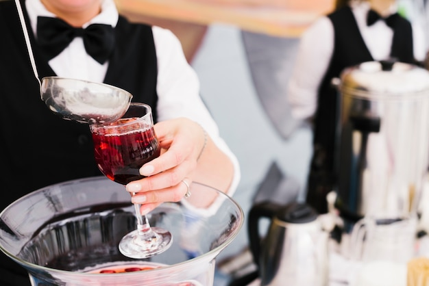 Server pouring sangria with ladle