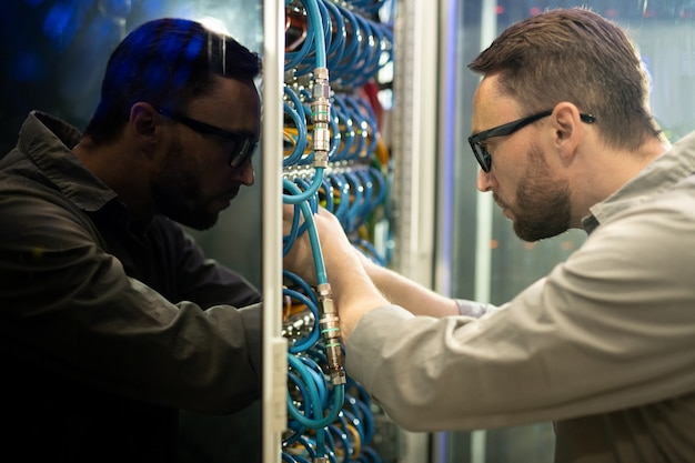 Server repairman connecting cables to supercomputer