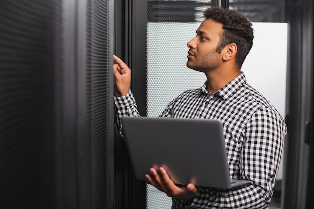 Server room. focused it guy using laptop and pointing at hardware