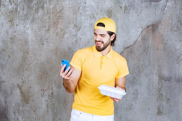 Сервисный агент в желтой форме держит пластиковую коробку для еды на вынос и принимает заказ по телефону.