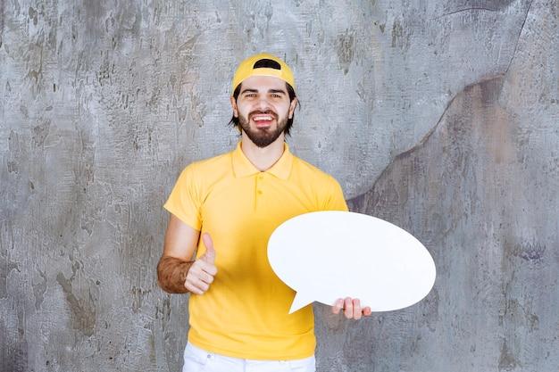 卵形の情報ボードを保持し、肯定的な手のサインを示す黄色の制服を着たサービスエージェント