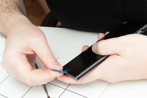 휴대폰 수리 서비스 센터입니다. 마법사가 스마트폰 덮개를 엽니다.