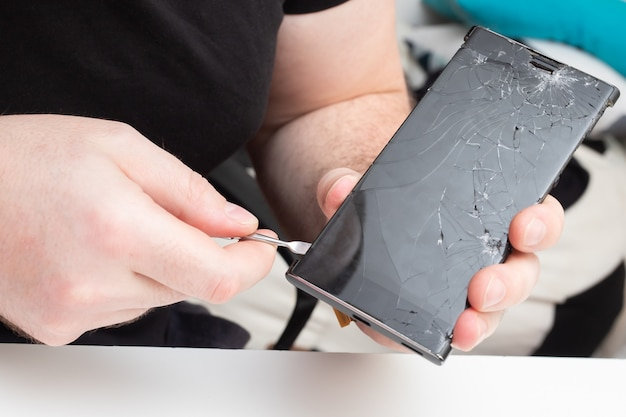 携帯電話の修理のためのサービスセンター。ウィザードはスマートフォンから画面保護ガラスを削除します