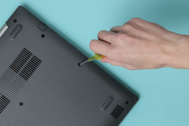 Service center laptop repair female hand screwdriver unscrews laptop bolts