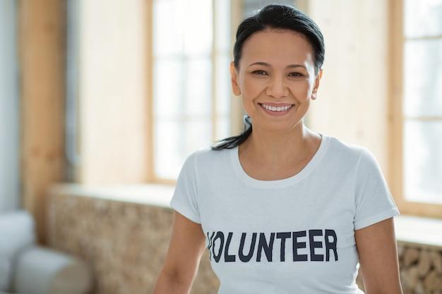 서비스 학습. 배경을 흐리게에 포즈를 취하고 카메라를 응시하는 동안 웃고있는 행복 낙관적 여성 자원 봉사자
