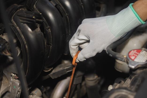 車のオイルエンジンをチェックするサービスマン、ハンドホールドオイルチェックスティックまたはオイルレベルゲージをクローズアップ