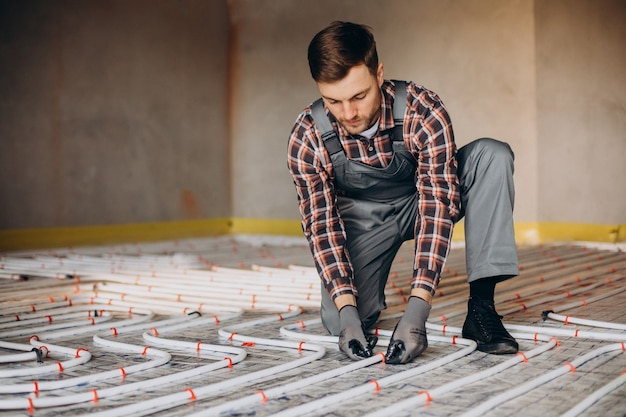 Service man instelling house heating system under the floor