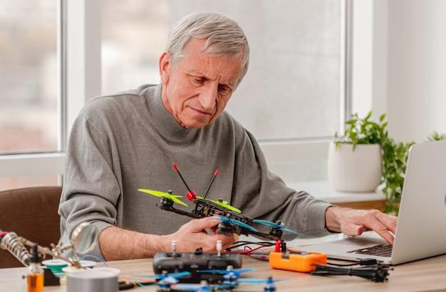 Обслуживающий персонал сидит с ноутбуком и смотрит на квадрокоптер в руках во время ремонта