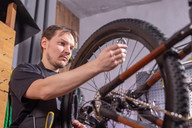 Концепция обслуживания, ремонта, велосипеда и людей - механик ремонтирует горный велосипед в мастерской