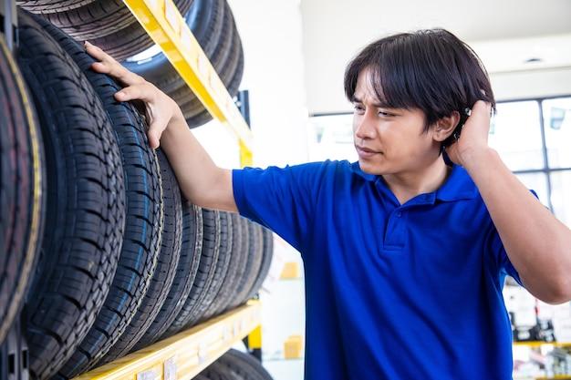 スーパーマーケットのモールでタイヤを購入するために触れて選択するサービススタッフの男性。