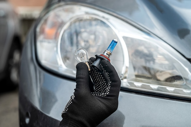 Service worker replaces halogen h7 lamp in passenger car headlight, repair auto concept