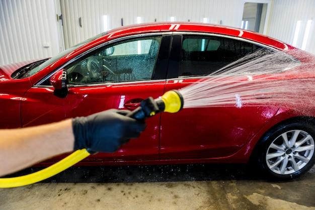 Работник службы моет машину на автомойке.