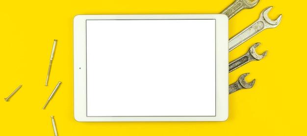 サービスワークスペーステンプレートとモックアップ画面、機器ツールを備えたワーカーテーブル上のタブレット付きバナー、黄色の背景、上面図、フラットレイ、コピースペースの写真