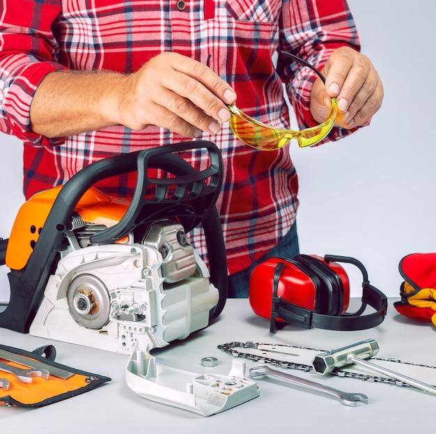 Сервисный мастер ремонтирует бензопилу в мастерской. ремонтник с оборудованием безопасности и бензопилой на верстаке.