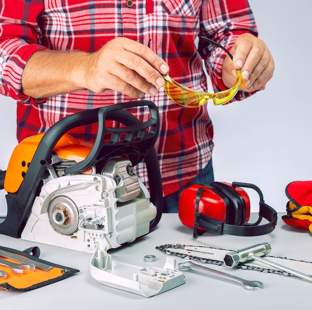 Serviceman is repairing a chainsaw in repair shop. repairman with safety equipment and chainsaw in workbench.