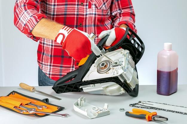 Serviceman is repairing a chainsaw  in repair shop