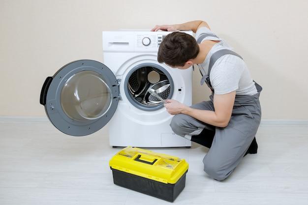 Serviceman repairs broken washing machine near beige wall