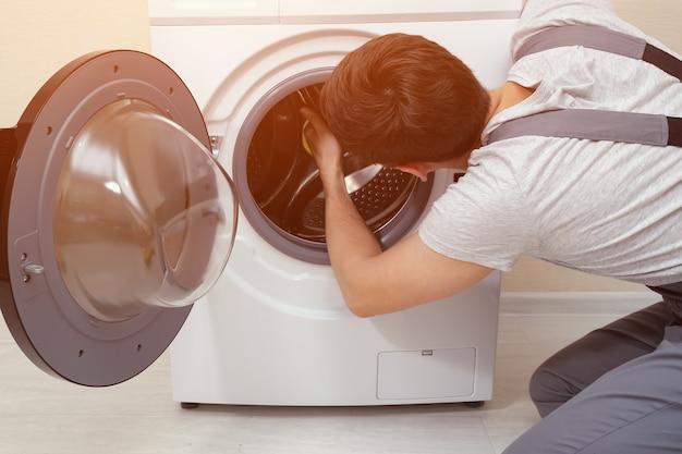 군인이 고장난 세탁기를 수리합니다.