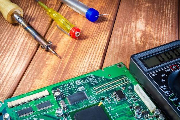 電子機器の製造および電子ボードの修理のためのサービス。木製の背景。