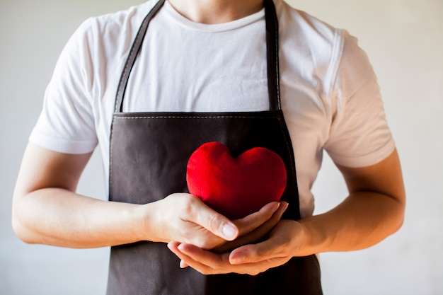 Servicing man in apron holding heart