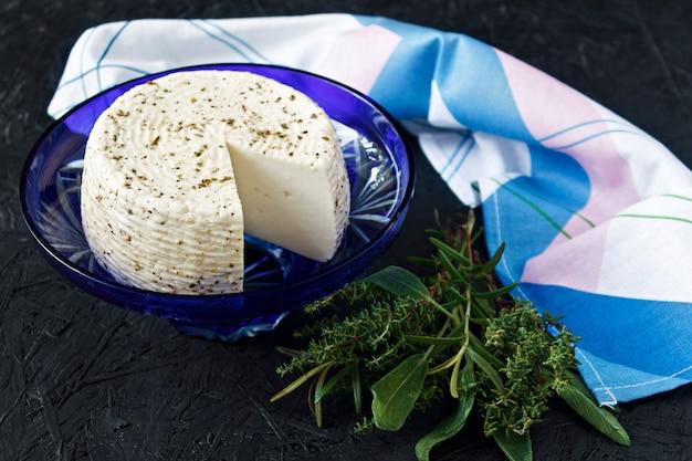黒の背景とservietteの皿の上のホワイトチーズ