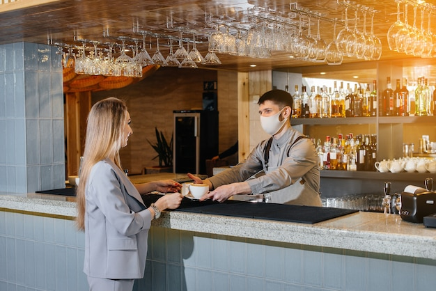 パンデミックの最中に、美しいカフェで若い女の子にマスクされたバリスタのおいしいナチュラルコーヒーを提供します。
