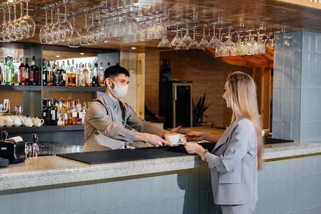 Подача бариста в маске вкусного натурального кофе молодой девушке в красивом кафе во время пандемии.