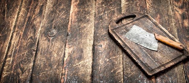Обслуживающий фон. старый топорик на разделочной доске. на деревянном столе.