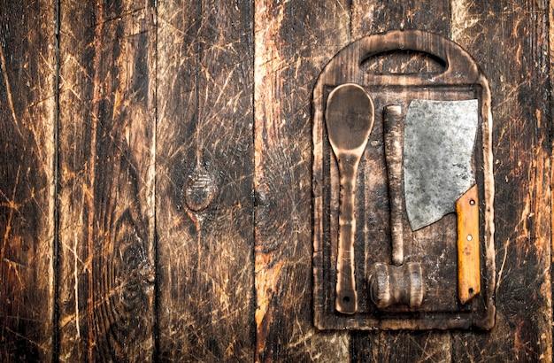 Обслуживающий фон. старые кухонные инструменты разделочная доска. на деревянном столе.