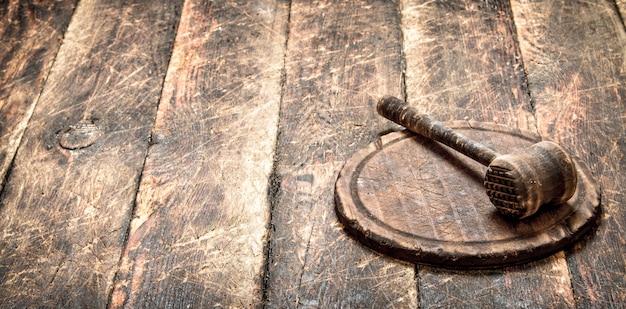 Обслуживающий фон. старый молоток мяса на разделочной доске.
